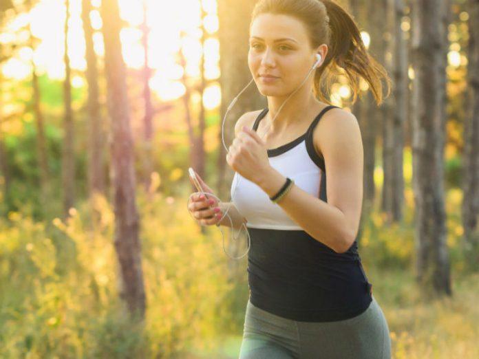 sportski obucena djevojka trci u sumi, tjelesna aktivnost