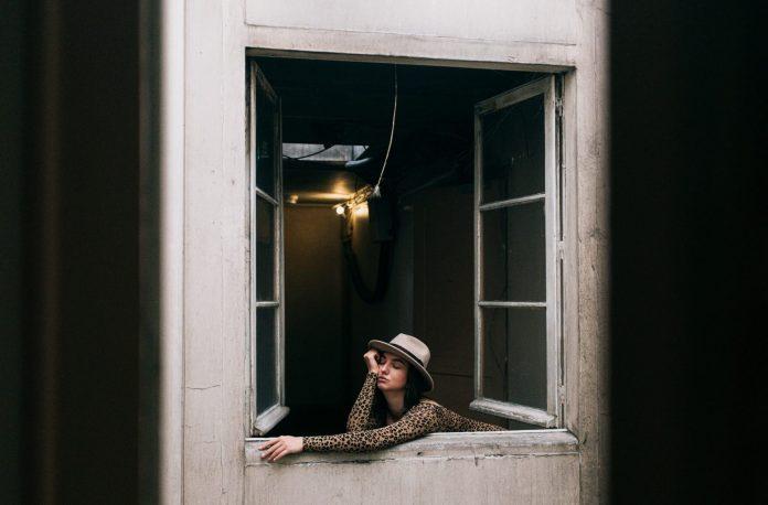 smeđokosa djevojka naslonjena na prozor